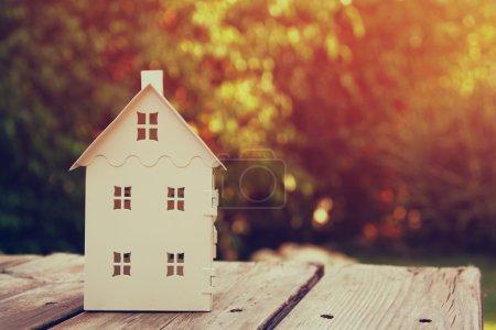 Photo pour Petit modèle de maison sur table en bois à l'extérieur au foyer sélectif de jardin. image filtrée. - image libre de droit