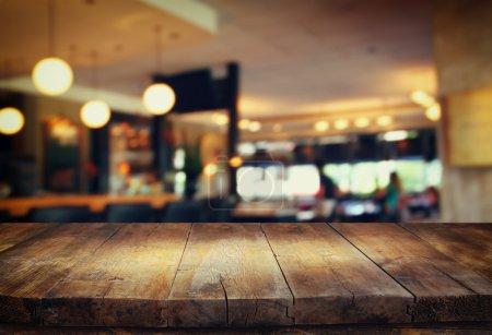 Photo pour Image de la table en bois devant le fond flou abstrait des lumières du restaurant . - image libre de droit