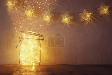Photo for Low key and vintage filtered image of fairy lights in mason jar with. selective focus. glitter overlay. - Royalty Free Image