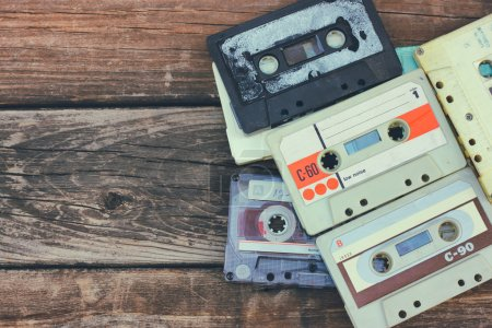 close up photo of cassette tape over wooden table . top view. retro filtered.