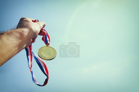 man hand raised, holding gold medal against Sky. award and victory concept. selective focus. retro style image