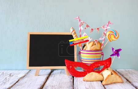 Hamantaschen cookies or hamans ears,noisemaker and mask next to blackboard for Purim celebration (jewish carnival holiday). selective focus