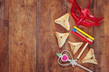 top view photo of Hamantaschen cookies or hamans ears,noisemaker and mask for Purim celebration (jewish carnival holiday). selective focus