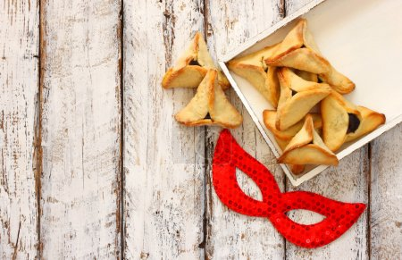 Hamantaschen cookies or hamans ears and red mask Purim celebration (jewish carnival holiday). selective focus