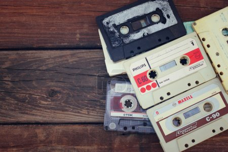 close up photo of cassette tape over wooden table . top view. retro filtered
