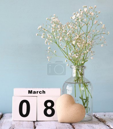Photo for Wooden March 8 calendar, next to heart and white flowers on old rustic table. selective focus - Royalty Free Image