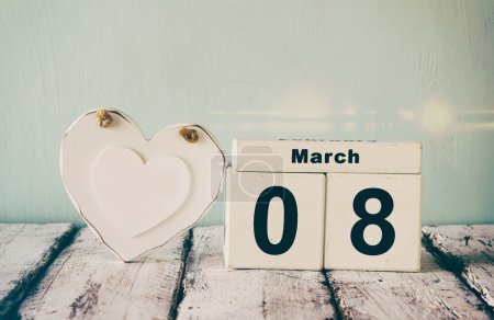 vintage filtered image of wooden March 8 calendar, next to white heart on old rustic table. selective focus