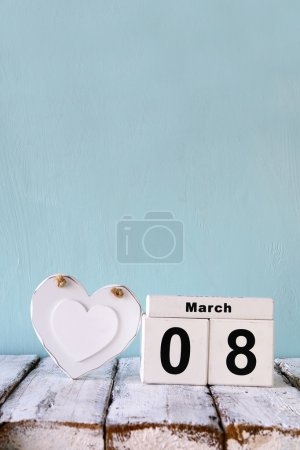 Photo for Vintage filtered image of wooden March 8 calendar, next to white heart on old rustic table. selective focus - Royalty Free Image