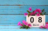Dřevěný kalendář 8. března, vedle fialové květy na staré modré rustikální stůl. selektivní zaměření
