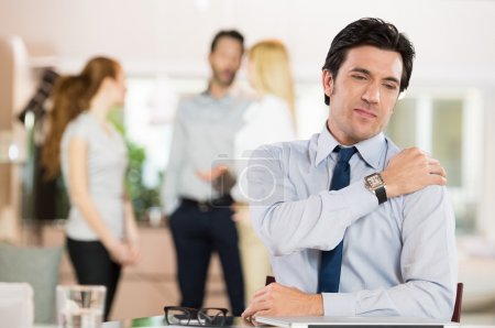 Photo for Portrait of a businessman at work suffering from shoulder pain. Portrait of stressed businessman holding shoulder and stretching after work. Mature businessman tired and stressed after working for long - Royalty Free Image