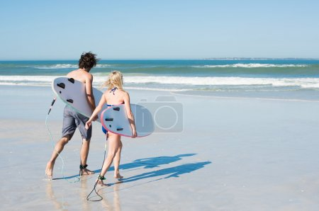 Couple surfing at ocean