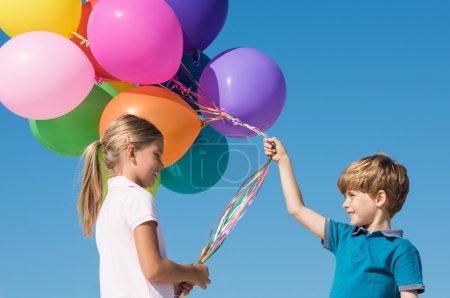 Photo pour Enfants jouant avec des ballons colorés sur fond de ciel bleu - image libre de droit