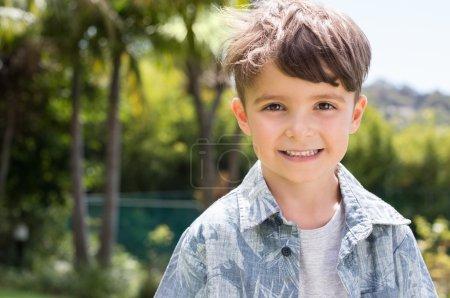 Photo pour Portrait d'un petit garçon heureux regardant la caméra. Un enfant heureux souriant avec un sourire de dents. Bel enfant en plein air décontracté . - image libre de droit