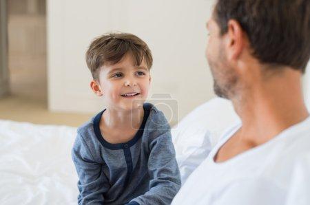 Photo pour Père et fils sont assis sur le lit et se parlent. Père et petit garçon souriant jouant assis sur le lit. Portrait d'enfant heureux écoutant son père à la maison - image libre de droit