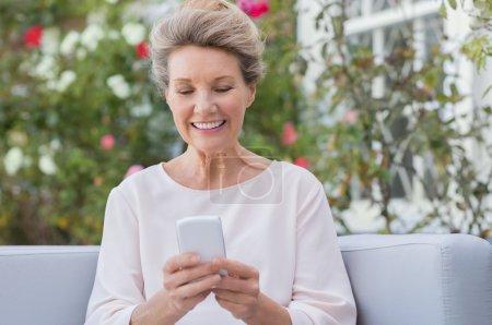 Photo pour Femme âgée messageries avec téléphone portable tout en étant assis sur le canapé dans le jardin. Une femme plus âgée envoie un message téléphonique avec son nouveau smartphone . - image libre de droit