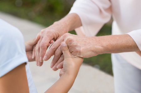 Photo for Closeup of grandmother and granddaughter holding hands. Old woman and little girl holding hands together. Closeup of hands of senior old woman and young girl outdoor - Royalty Free Image