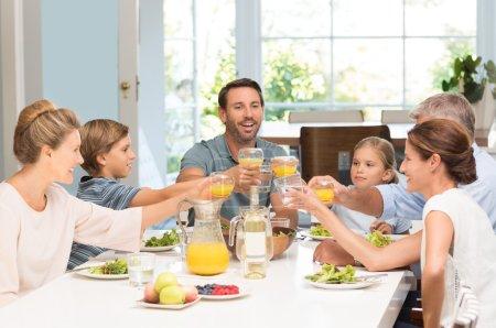 Foto de Familia sonriente levantando vasos juntos en la cocina. Padres felices con hijos y abuelos celebrando junto con un brindis. Alegre familia levantando tostadas con jugo en la mesa de comedor . - Imagen libre de derechos
