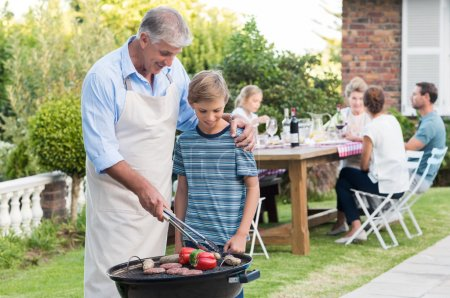 Grandfather cooking with grandson