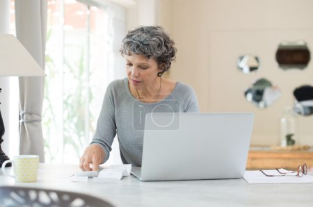 Photo for Senior woman working on home finance. Mature woman checking bills at home. Older woman checking pension approval certificate with laptop at home. - Royalty Free Image