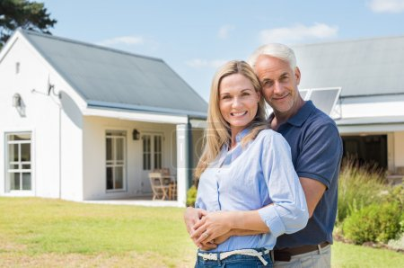 Cheerful senior couple standing outside their new ...