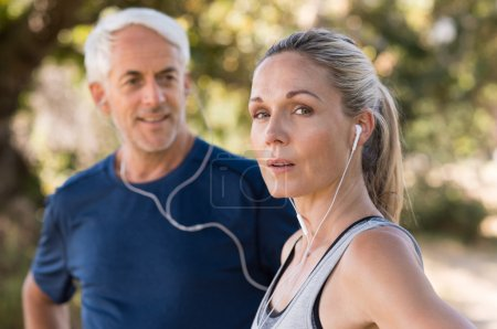 Photo for Senior couple resting after a long run in the park. Tired mature woman listening to music while relaxing after jogging. Senior woman looking at camera after training outdoor. - Royalty Free Image