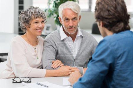 Photo pour Couple de personnes âgées réunion agent immobilier. Couple de personnes âgées réunion conseiller financier pour les investissements. Heureux homme mature et femme écoute de divers plans d'investissement pour leur retraite. - image libre de droit