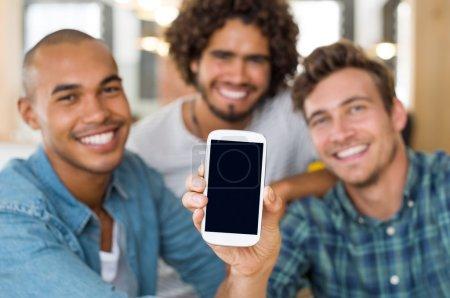 Photo pour Jeunes amis montrant l'écran noir du smartphone sur la caméra. Trois jeunes hommes assis dans un café à l'aide d'un smartphone. Trois gars tenant un téléphone portable avec écran vide prêt pour votre texte ou image - image libre de droit