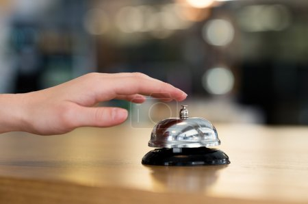 Photo for Close up of woman hand ringing bell at hotel at reception desk. Closeup of female hand ringing service bell - Royalty Free Image