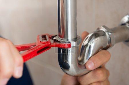 Photo pour Gros plan de fixation tuyau avec clé de plombier - image libre de droit