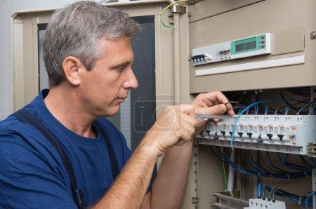 Repairman Fixing An Electric Switchboard Indoor...