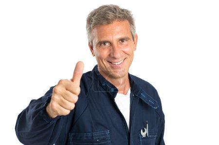 Foto de Retrato de confianza madura mecánico gesticular pulgar arriba signo aislado en blanco Backgriund - Imagen libre de derechos