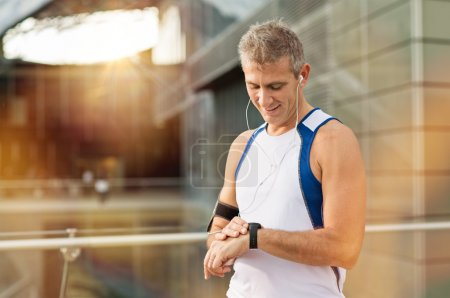 Photo for Portrait Of Happy Mature Man With Heart Rate Monitor On Wrist - Royalty Free Image