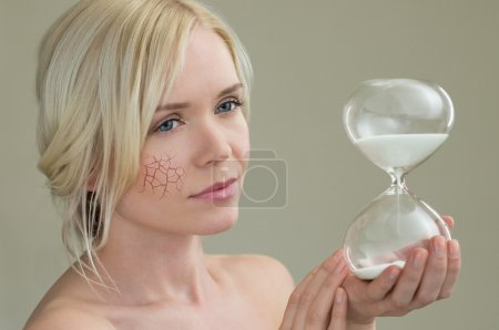 Young woman holding hour glass