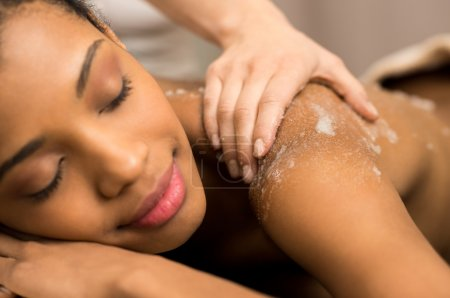 Spa therapist applying scrub salt on young woman b...