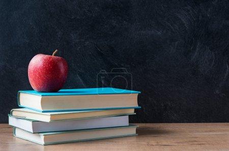 Photo pour Apple et une pile de livres sur le bureau avec tableau noir en arrière-plan - image libre de droit