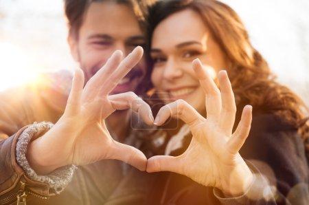 Photo pour Gros plan portrait de couple avec coeur et symbole d'amour des doigts - image libre de droit