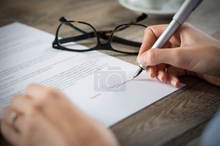 Photo for Closeup shot of a woman signing a form. She's writing on a financial contract. - Royalty Free Image