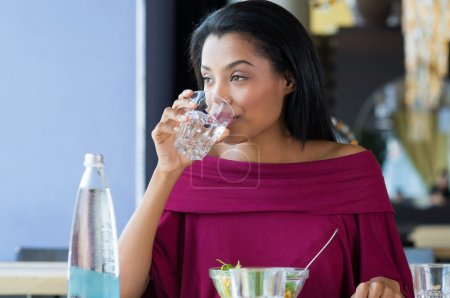 Photo for Closeup shot of young woman drinking a glass of water. African girl drinking water - Royalty Free Image