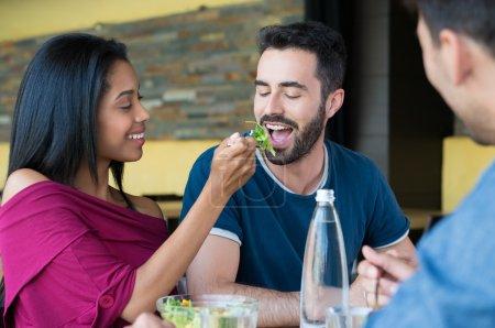 Young woman feeding salad to man