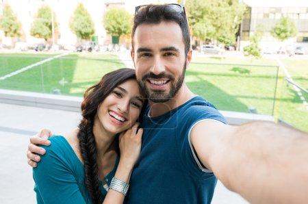Photo pour Closeup coup de jeune couple prenant selfie extérieure. Jeune homme, prenez une photo avec sa petite amie. Karine souriant couple prenant un selfie à une journée d'été - image libre de droit