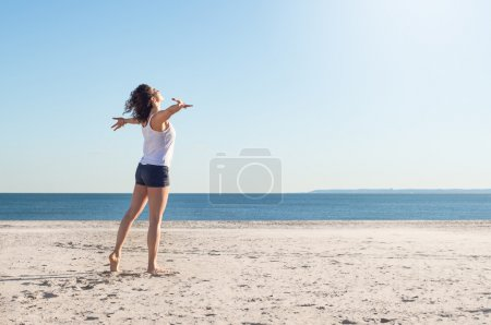 Photo pour Happy young woman with arms outstretched at beach on a bright morning. Beautiful young woman with arms stretched out standing on a beach. Happy young woman feelling good and relaxing at the beach. - image libre de droit