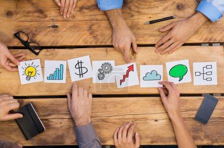 Photo pour Des hommes d'affaires organisant différents concepts d'affaires sur une table en bois. Stratégie des cartes blanches utilisée par les gens d'affaires. Gens d'affaires stockage du cerveau pour de nouvelles solutions tout en plaçant différentes cartes dans le bureau . - image libre de droit
