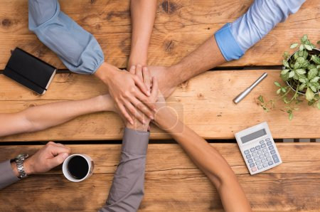 Photo for Closeup of business colleagues with their hands stacked. Business team showing unity with their hands together. Close up of business partners making pile of hands at meeting. Concept of united business team work. - Royalty Free Image