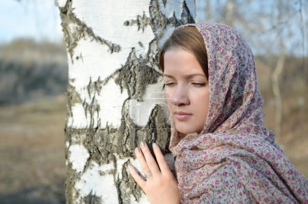 Russian girl in a scarf in a birch forest close up