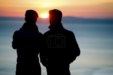 Photo pour Silhouette de deux jeunes hommes parlant au coucher du soleil - image libre de droit