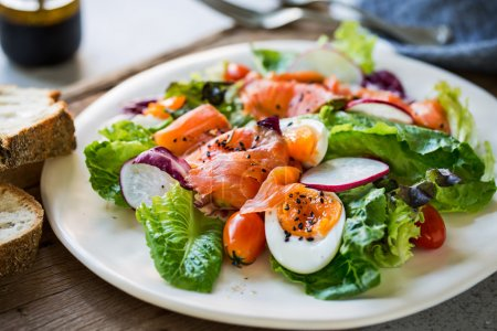 Photo for Smoked Salmon with boiled eggs salad by some bread - Royalty Free Image