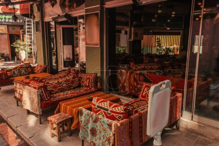 Tables and sofas with oriental ornaments in outdoors cafe on sidewalk in Istanbul, Turkey