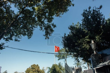 Turkish flag with blue sky at background on urban street in Istanbul