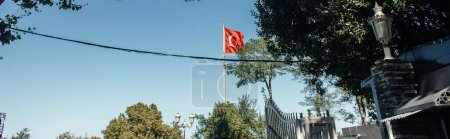 Red trkish flag with blue sky at background on street in Istanbul, banner