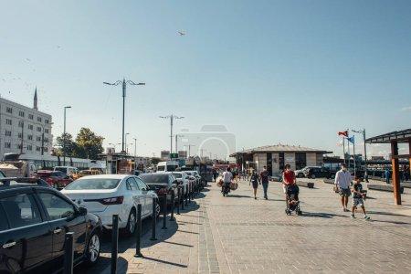 ISTANBUL, TURKEY - NOVEMBER 12, 2020: People walking on sidewalk near cars on urban street